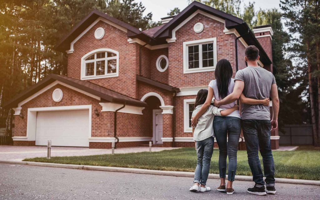 happy family standing in front of new brick home