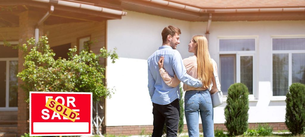 newlywed-couple-standing-in-front-yard-of-their-new-housex2000