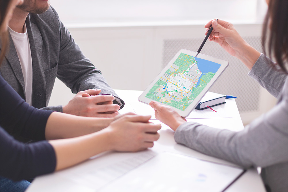 real-estate-agent-showing-a-couple-a-map-of-Rochester,-NY-on-a-tablet